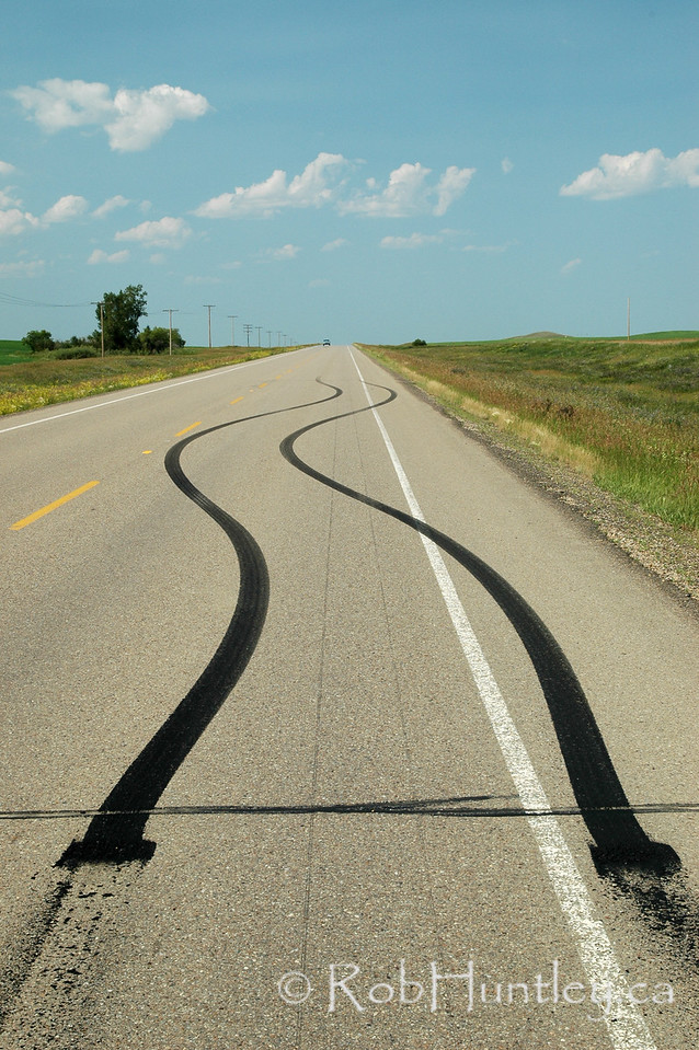 Laying rubber. Leaving tracks on the pavement on a country road in southern Saskatchewan. © Rob Huntley  This is a Rights Managed (RM) image. License this photo on Getty Images