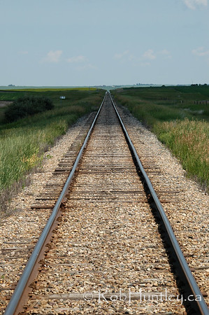 Railroad tracks disappearing in the distance and into the shadow of an overhead cloud. In southern Saskatchewan. © Rob Huntley