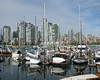 Vancouver, BC boats moored in the harbor and highrises as viewed from Granville Island.