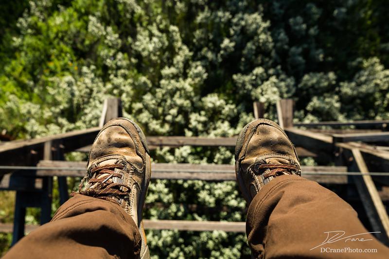 Feet dangling from abandoned railroad trestle