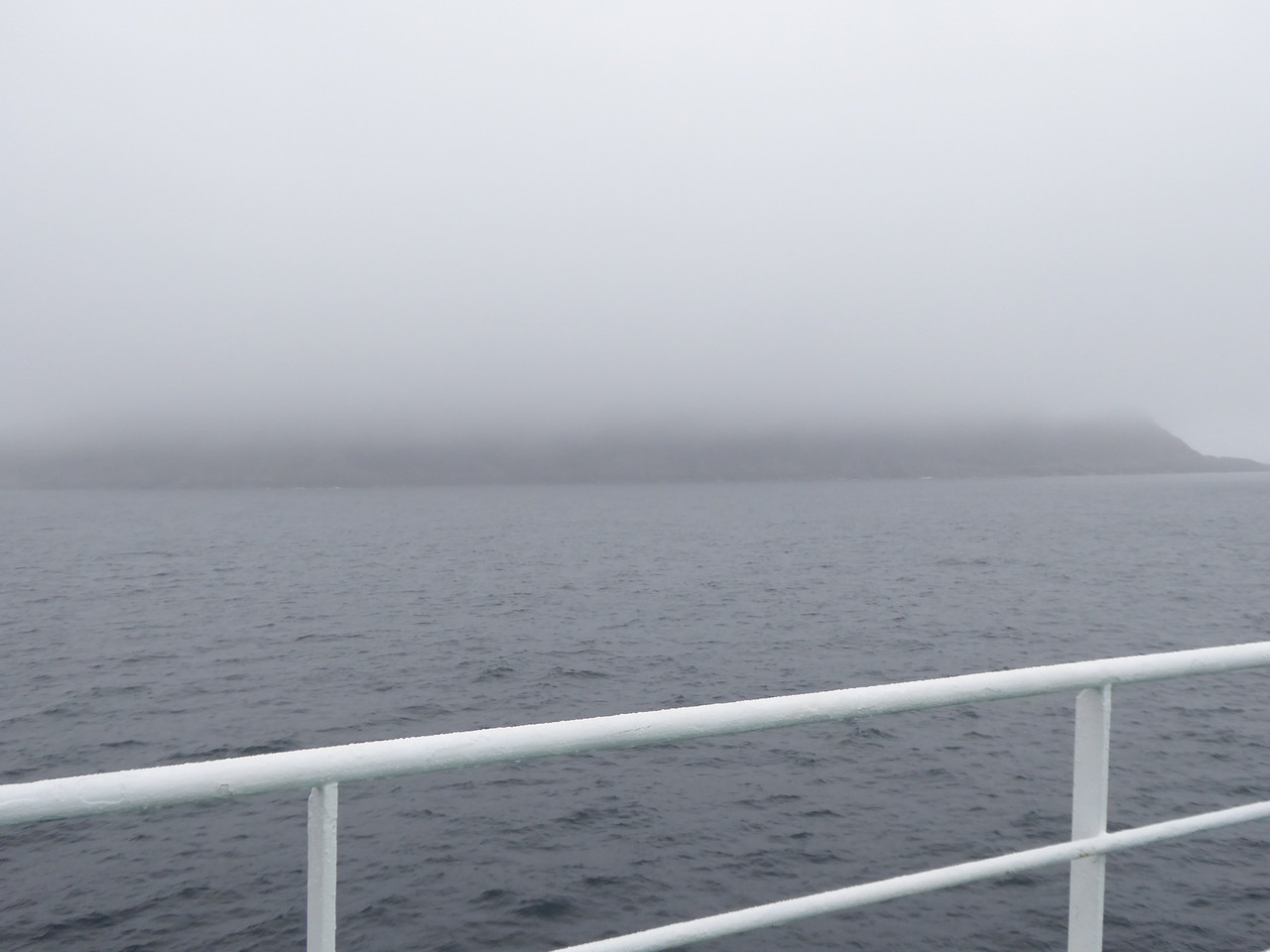 Back on board, Monumental Island is barely visible in the fog.