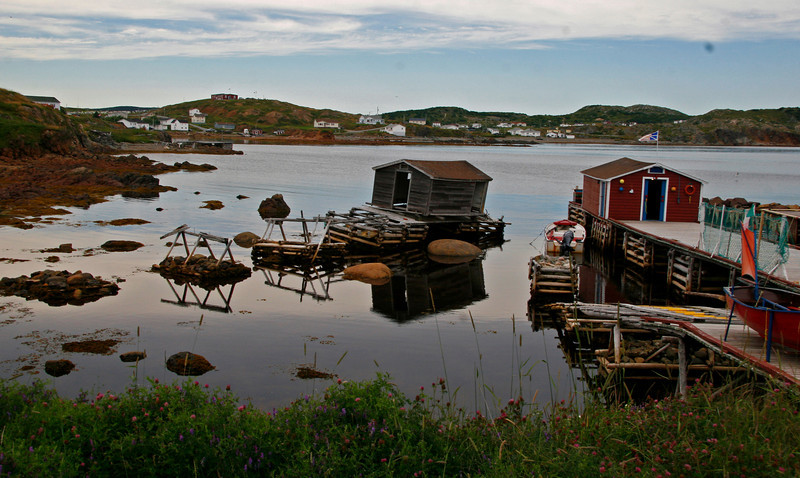 This is a quiet cove  on a spit of land that reaches out into Notre Damm Bay in NE NF The old building is a rotting Salt Box house where in days of Cod they were split, salted and dried on wood racks. The red building on the right is Melvin Horwood's  Mini Musem where he has exhibits about icebergs and the days of Cod.