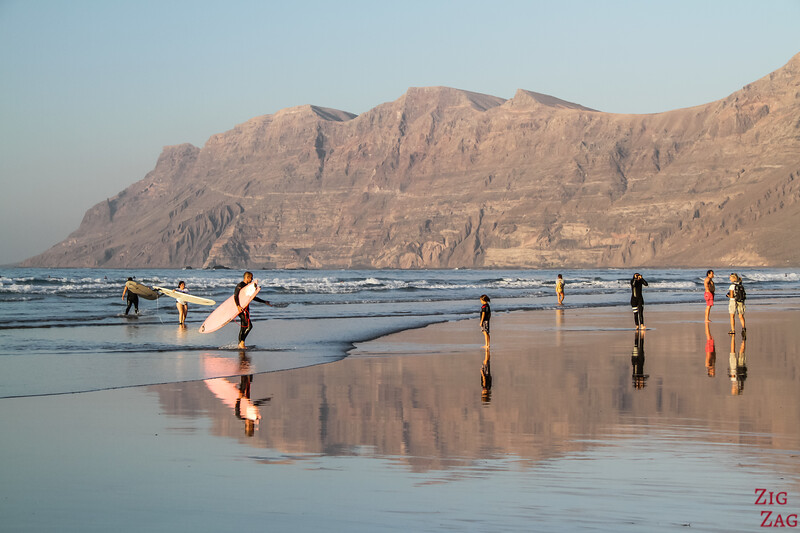 Best places in Lanzarote - reflection of the cliffs and surfers at Famara Beach at sunset