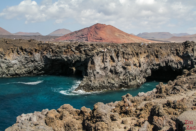 Best places in Lanzarote - Basalt formation by the sea with turquoise water, dark rock and red volcano