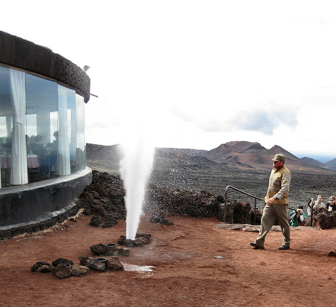 Pouring water down a pipe sunk into the active volcanic ground produces an artificial geyser. El Diablo restaurant, Timanfaya National Park, Lanzarote.