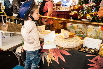 Boy in cycle helmet watches on at Antibe Market, France.