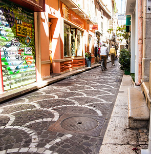 Antibes street scene, patterned cobblestones in narrow street.