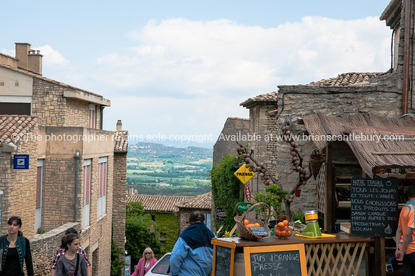 Gordes, view between cafes and buildings over the riviera countryside, Cote d'Azur, France.