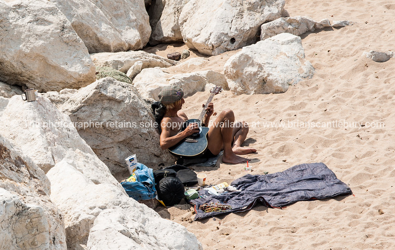 Beachgoer playing guitar on beach, Cannes, Cote d'Azur.