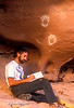 Model Released, Man Writing in a Journal below pictograph of Hands created by Ancestral Pueblo Culture, Canyonlands National Park, Souteastern Utah, USA, North America