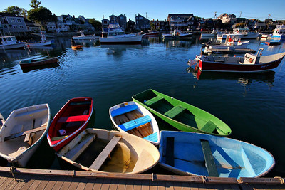 Rockport, Mass. Fishermen use these small shuttle boats to get to their boats in the harbor, such as the man in the orange boat is doing in this photo.