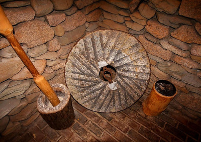 A spare mill stone graces one corner of the mill's lower level.