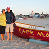 An older couple enjoys a walk in the early morning on the beach at Cape May, standing next a life saving boat