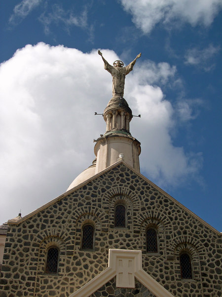 Statue of God atop church has outstreached arms overlooks the island of Martinique
