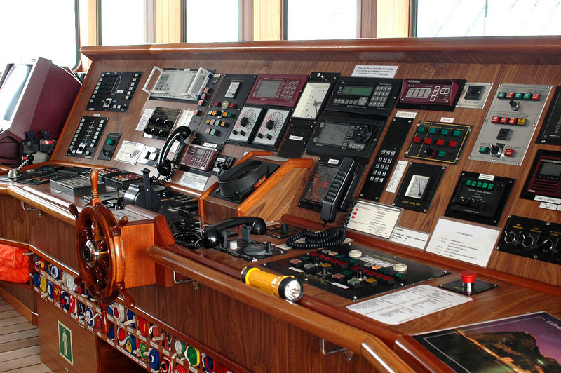 The bridge. The flag of each nation potentially visited is stowed beneath the wheel and raised as we come into port. The captain came in soon after I took this picture to ask us what we had touched. We assured him only the red buttons.