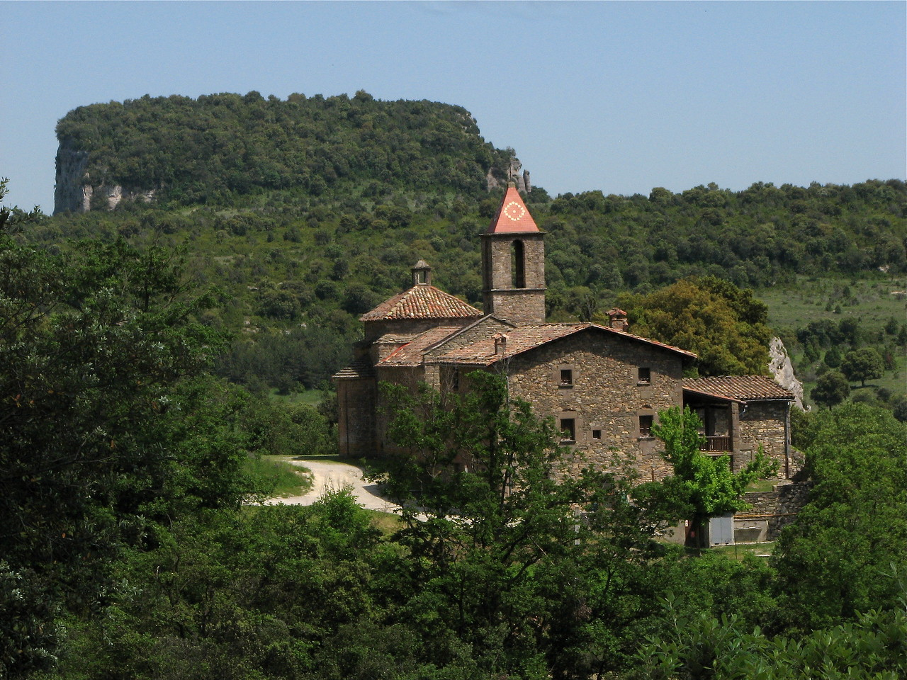 Old church in the hills south of Rupit, Catalonia, Spain.  In the background is a limestone outcrop atop a plateau.