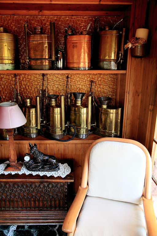 Antique copper pesticide spray cans on display in the lobby of the Hostal de la Gloria, Viladrau, Spain