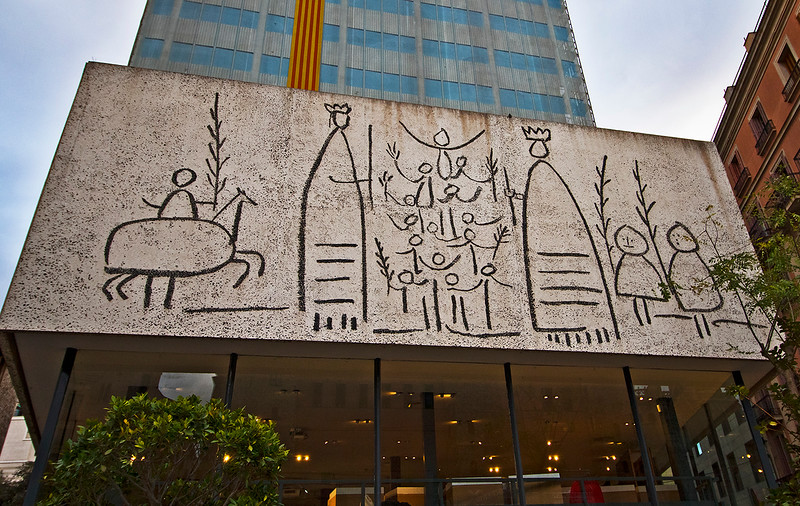 """One of three panels, by Picasso, located on a building in front of our hotel. The  red and gold striped banner, known as la Senyera, is a symbol of the supporters of Catalunya's independence. A story says that in long-ago a battle against a Moorish governor, one fighter was severely wounded. The Frankish ruler (Charles the Bald) plunged his hand into the wound and wiped his four fingers across a golden shield. He held the shield high and led the troops to victory. On the Catalan flag the four red stripes are known as """"Els Quatre Dits de Sang"""" (The Four Fingers of Blood)."""