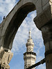 Roman arch from the gate to the Roman Temple of Jupiter frames a minaret in the 7th century Umayyad Mosque