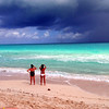 Two girls looking at a waterspout off in the distance.