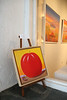 Painting of giant tomato on a beach in a gallery window.