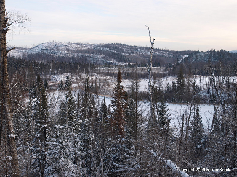We parked at the Kekekabic Trail head and hiked 1/2 mile to the Centennial Trailhead.  A steep, but brief hike leads to first of many dramatic views.   Here we see a old railroad grade curving from right to mid of the photo and Gunflint Trail running left/ right in front of the background hillside.