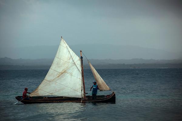 Local fishermen sail a small boat