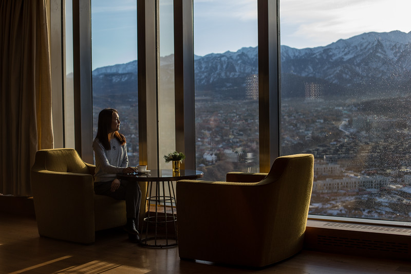 A female tourist enjoys a cup of tea overlooking the mountains of Almaty, Kazakhstan.