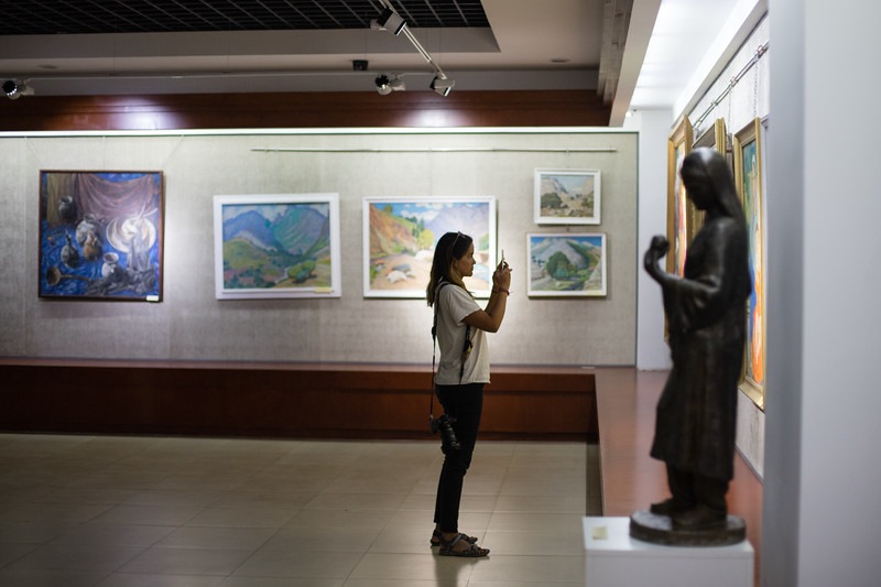 A foreign tourists stops for a photo in the Tajikistan National Museum in Dushanbe.