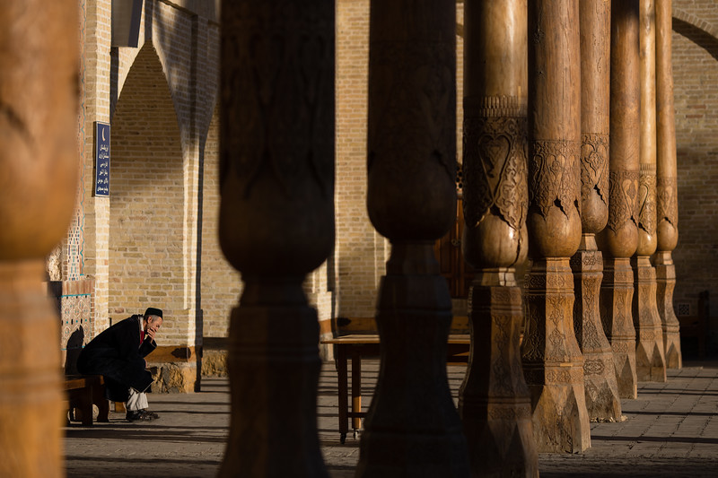 A lone worshipper sits on a bench in the portio of Bolo-Hauz Mosque in Bukhara, Uzbekistan.