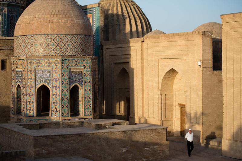 A local man walking through the Shah-i-Zinda Mausoleum complex in Samarkand, Uzbekistan.