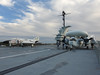 The top deck of the carrier has an array of planes.