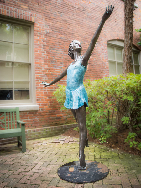 A metal sculpture of a lady I saw between a couple of buildings