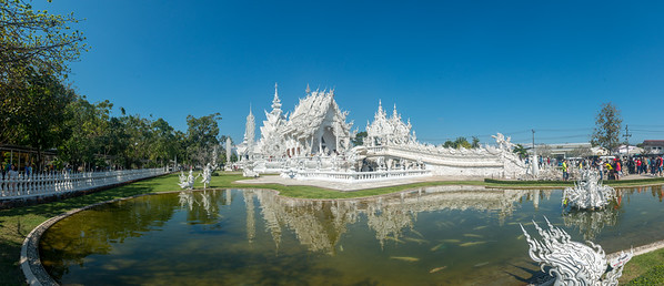 Wat Rong Khun White Temple (วัดร่องขุ่น) panoramic view Contemporary Buddhist temple drawing massive crowds with its unique, intricate white exterior. Wat Rong Khun, also known as the White Temple, is a contemporary, unconventional, privately-owned art exhibit in the style of a Buddhist temple in Chiang Rai Province, Thailand.