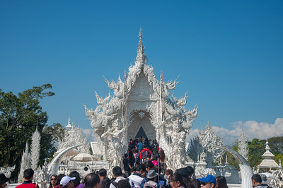 Large crowds at Wat Rong Khun White Temple (วัดร่องขุ่น)  Contemporary Buddhist temple drawing massive crowds with its unique, intricate white exterior. Wat Rong Khun, also known as the White Temple, is a contemporary, unconventional, privately-owned art exhibit in the style of a Buddhist temple in Chiang Rai Province, Thailand.