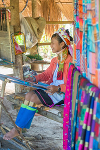 Young Karen Lady operating the handloom. Long Neck Karen in Chiang Rai, Chang Wat Chiang Rai, Thailand The Karen are a tribal group who have historically lived in the hills on the Myanmar (formerly Burma) side of the Thai border. Best recognized for their elongated necks, the Karen women wear heavy brass rings around their necks, forearms, and shins. There is a lot of criticism surrounding this. From human-zoo to women earning a honest living and not being prosecuted. Depending on which side of the argument you are. When we first arrived each woman was stationed by her own hut busy working on the knitting looms and it initially felt a little bit like a staged atmosphere but talk and spend time and it feels not very different than other villages. Controversy or not, had mixed feelings on this.