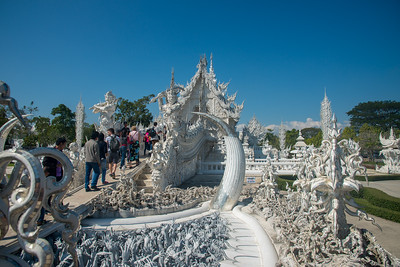 Various depictions of Buddhist teaching at Wat Rong Khun White Temple (วัดร่องขุ่น)  The hands in the foreground represent miseries in human life and how we have to take the path of Dharma. Contemporary Buddhist temple drawing massive crowds with its unique, intricate white exterior. Wat Rong Khun, also known as the White Temple, is a contemporary, unconventional, privately-owned art exhibit in the style of a Buddhist temple in Chiang Rai Province, Thailand.