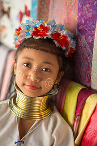 Karen Long Neck girl's portrait. Long Neck Karen in Chiang Rai, Chang Wat Chiang Rai, Thailand The Karen are a tribal group who have historically lived in the hills on the Myanmar (formerly Burma) side of the Thai border. Best recognized for their elongated necks, the Karen women wear heavy brass rings around their necks, forearms, and shins. There is a lot of criticism surrounding this. From human-zoo to women earning a honest living and not being prosecuted. Depending on which side of the argument you are. When we first arrived each woman was stationed by her own hut busy working on the knitting looms and it initially felt a little bit like a staged atmosphere but talk and spend time and it feels not very different than other villages. Controversy or not, had mixed feelings on this.