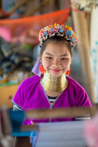 Karen Long Neck girl on the handloom. Long Neck Karen in Chiang Rai, Chang Wat Chiang Rai, Thailand The Karen are a tribal group who have historically lived in the hills on the Myanmar (formerly Burma) side of the Thai border. Best recognized for their elongated necks, the Karen women wear heavy brass rings around their necks, forearms, and shins. There is a lot of criticism surrounding this. From human-zoo to women earning a honest living and not being prosecuted. Depending on which side of the argument you are. When we first arrived each woman was stationed by her own hut busy working on the knitting looms and it initially felt a little bit like a staged atmosphere but talk and spend time and it feels not very different than other villages. Controversy or not, had mixed feelings on this.