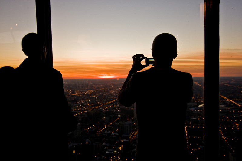 Title: Picturing the Setting Sun<br /> Date: November 2010<br /> A person catching the setting sun in the west; from the observation deck of the John Hancock Building.