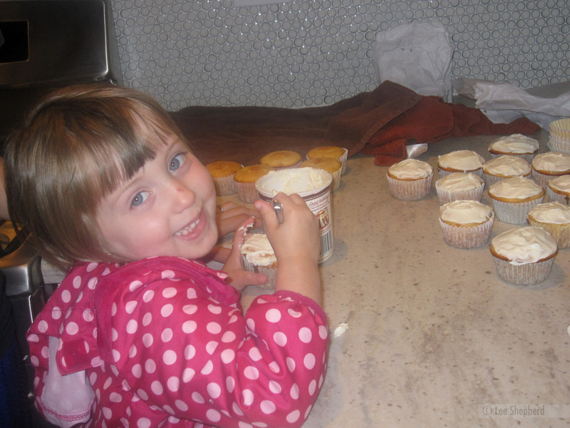 Helping frost Aunt Joann's birthday cupcakes