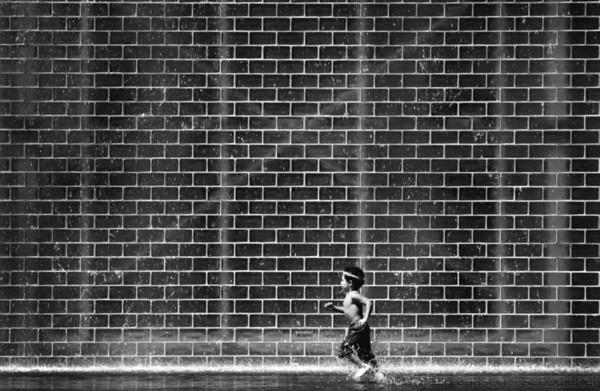 Boy running through a fountain in Millenium Park.