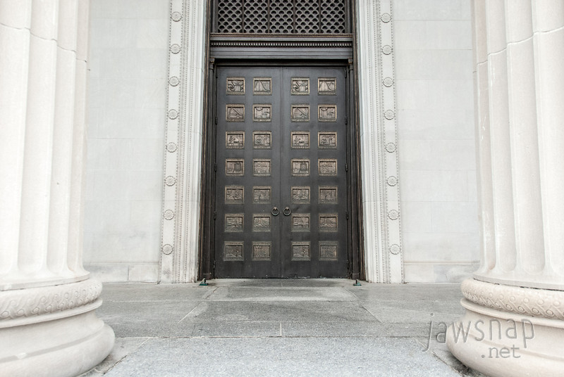 """<span id=""""title"""">Main Entrance</span> The building that houses the Museum of Science and Industry is one of the few buildings that's still around from the World's Columbian Exposition in 1893. I found it quite curious that you first descend into a cavernous basement when you enter, then go up huge escalators to get to the exhibits. The whole layout was kind of baffling, and you never see the outside when you're in the museum. Back before it was the MSI, however, these were the main doors. Each panel depicts some sort of industry, like 'Transportation' or 'Mining'."""