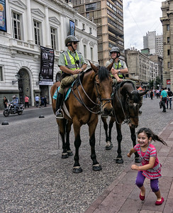 A little girl delighting in the horses running to tell her friends.