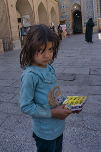 A young street child selling gum to tourists visiting the mosque.