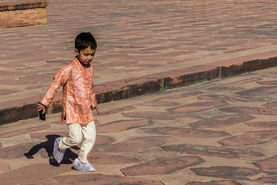 A child playing near red sandstone mosque in the Taj Mahal complex. it was obligatory according to the Muslim law for each mausoleum to have a place of worship  nearby.