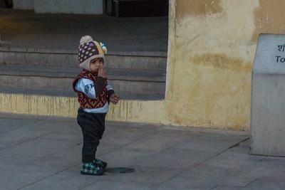 A liitle boy perhaps waiting for a parent outside the public toilets.