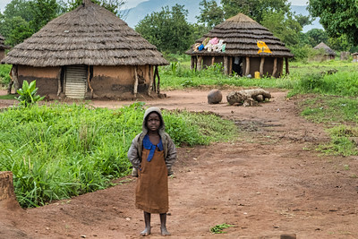 A child and some homes as seen from the road.  You can still see the beautiful mountains in the background.