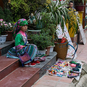 Child selling embroidery for which the area is known