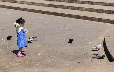 Little girl feeding pigeons just outside the kasbah